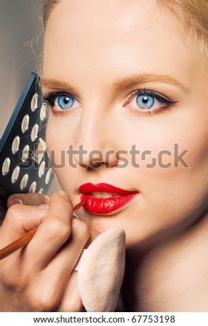 Portrait of a woman putting on lip liner. - stock photo