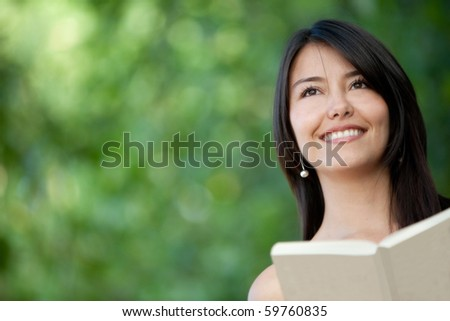 Portrait of a woman reading a book outdoors - stock photo