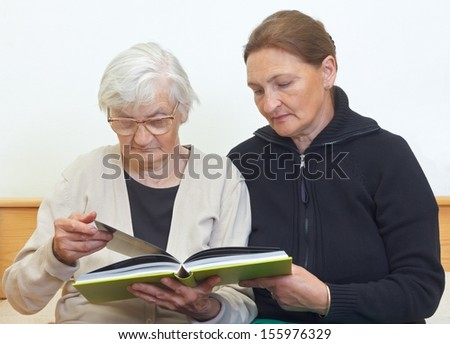 Portrait of a woman reading a book with her elderly mother - stock photo
