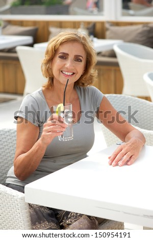 Portrait of a woman relaxing on vacation with glass of water at outdoors restaurant