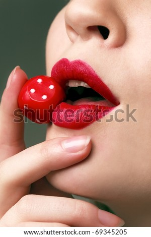 Portrait of a woman's face holding in mouth a red dice - stock photo