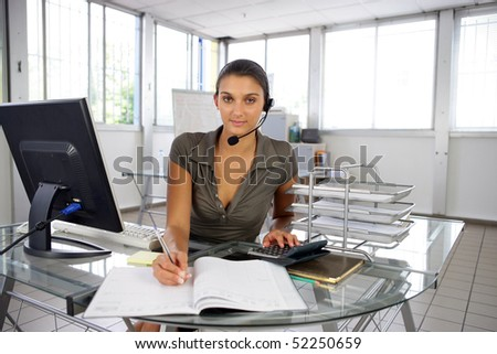 Portrait of a woman sat at a desk with a headphone talkback