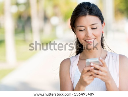 Portrait of a woman sending text message from her phone - stock photo