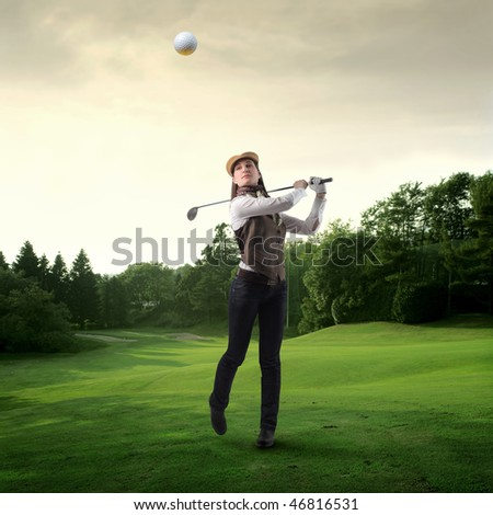 Portrait of a woman shooting a golf ball on a green meadow - stock photo