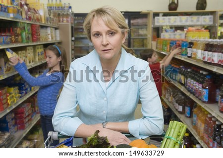 Portrait of a woman shopping with son and daughter in supermarket - stock photo