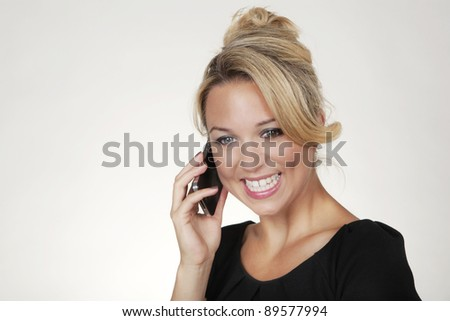 portrait of a woman shot in the studio on a white background on her mobile phone - stock photo