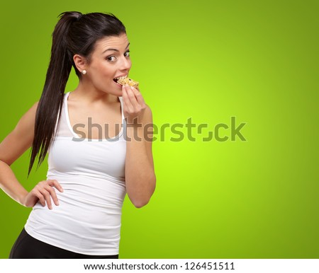 Portrait Of A Woman showing Granola Bar isolated on green background - stock photo