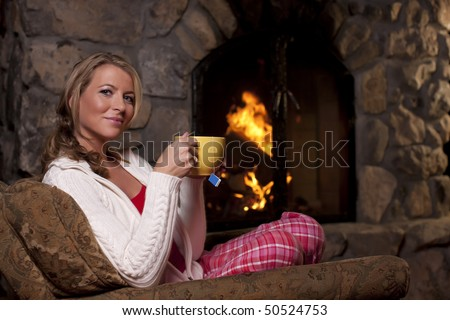 Portrait of a woman sitting in an armchair by a fireplace. She is holding a cup of tea and smiling at the camera. Horizontal format. - stock photo
