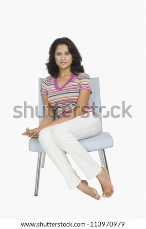 Portrait of a woman sitting on a chair - stock photo