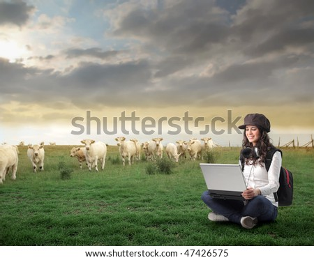 Portrait of a woman sitting on a green meadow and working on a laptop - stock photo