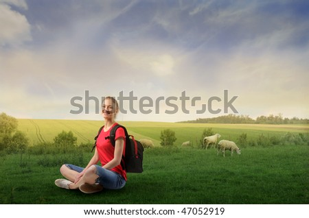Portrait of a woman sitting on a green meadow with two lambs on the background