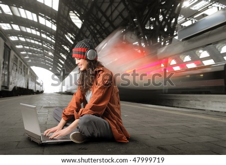 Portrait of a woman sitting on a platform and working on a laptop - stock photo