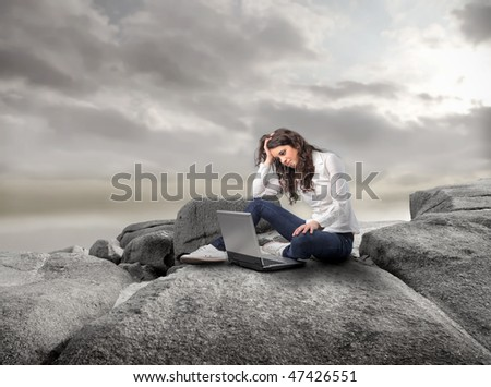 Portrait of a woman sitting on a rock and working on a laptop - stock photo