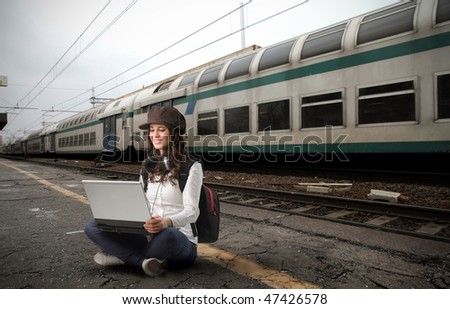 Portrait of a woman sitting on the platform of a train station and working on a laptop - stock photo