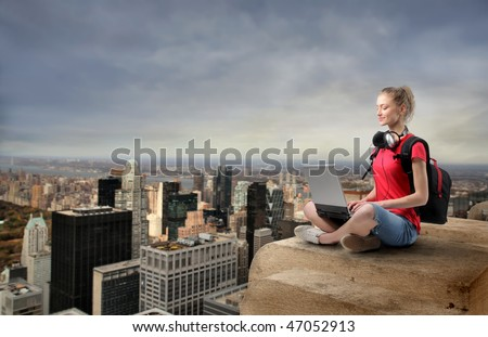 Portrait of a woman sitting on the top of a skyscraper with cityscape on the background - stock photo