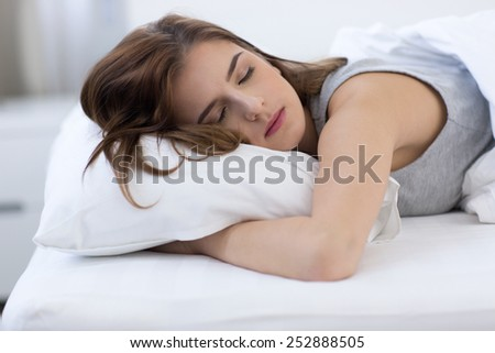 Portrait of a woman sleeping on the bed at home - stock photo