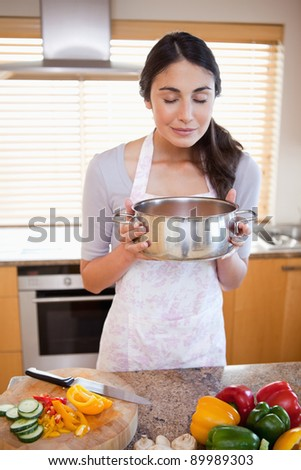 Portrait of a woman smelling a sauce in her kitchen - stock photo
