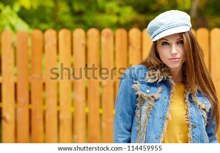 portrait of a woman smiling against a wooden wall