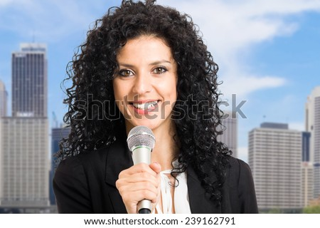 Portrait of a woman speaking in a microphone - stock photo