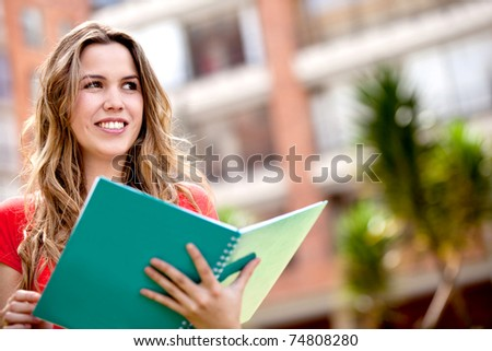 Portrait of a woman studying outdoors with a notebook - stock photo