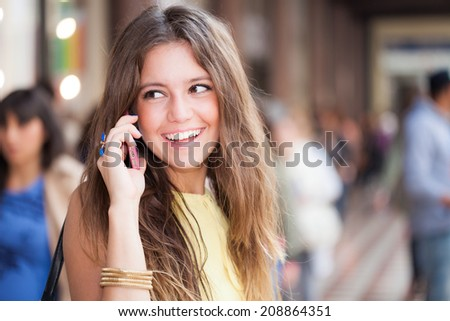 Portrait of a woman talking on the cell phone in a crowded street - stock photo
