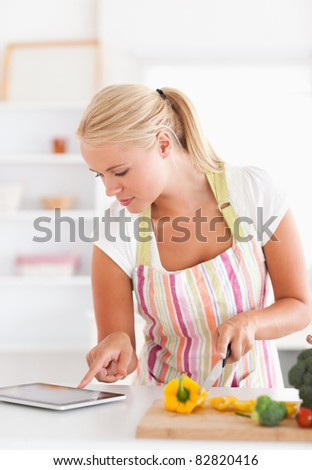 Portrait of a woman using a tablet computer to cook in her kitchen - stock photo