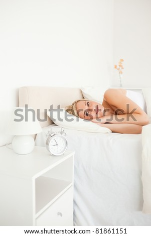 Portrait of a woman waking up and an alarm clock with the camera focus on the model - stock photo
