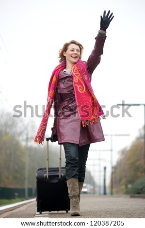 Portrait of a woman waving her hand on train station platform - stock photo