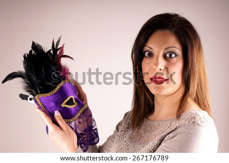 Portrait of a woman wearing a carnival mask - stock photo