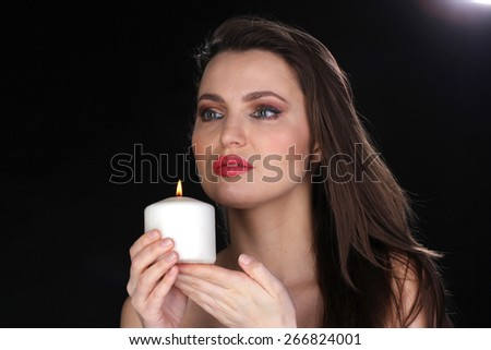 Portrait of a woman with a candle. Black background. Studio shot. - stock photo