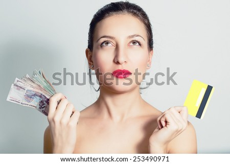 Portrait of a woman with a credit card and cash. - stock photo
