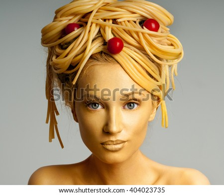 Portrait of a woman with a lot of pasta on head. Pasta with tomatoes. Girl with food hair style. Body painting. - stock photo
