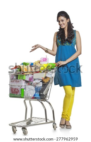 Portrait of a woman with a shopping cart gesturing - stock photo