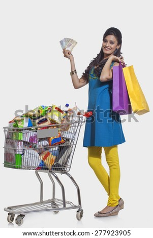 Portrait of a woman with a shopping cart , shopping bags and currency - stock photo
