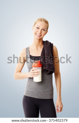 Portrait of a woman with a towel around her neck holding a protein shaker and standing against at isolated background.