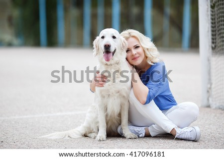 Portrait of a woman with beautiful dog playing outdoors. Beautiful woman playing with golden retriever. Outdoor portrait. series.