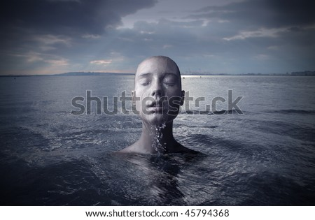 Portrait of a woman with close eyes who emerges from water - stock photo