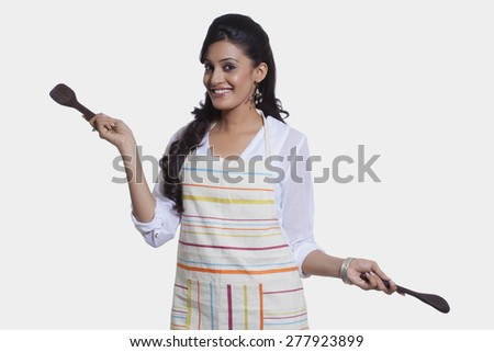Portrait of a woman with cooking utensils - stock photo