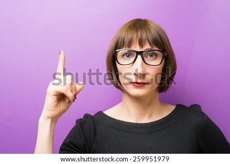 portrait of a woman with glasses forefinger up - stock photo