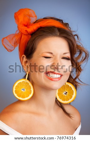 Portrait of a woman with grin slices of oranges as earring winkling - stock photo