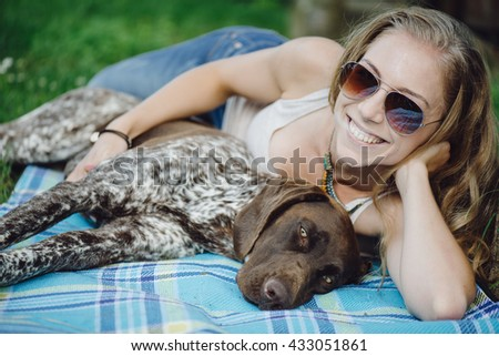 Portrait of a woman with her beautiful dog lying outdoors - stock photo