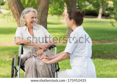 Portrait of a woman with her mature mother sitting in wheel chair at the park - stock photo