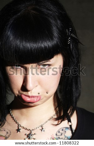 portrait of a woman with piercing and pout - stock photo