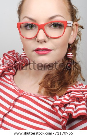 Portrait of a woman with red lips make-up in modern red glasses over grey isolated background