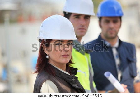 Portrait of a woman with safety helmet on a construction site - stock photo