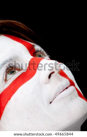 Portrait of a woman with the english flag paited on her face - over a black background - stock photo