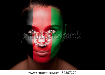 Portrait of a woman with the flag Afghanistan painted on her face. - stock photo