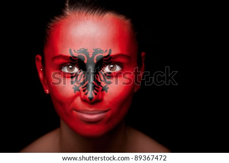 Portrait of a woman with the flag of the Albania painted on her face. - stock photo