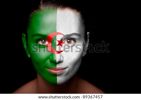 Portrait of a woman with the flag of the Algeria painted on her face. - stock photo