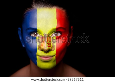 Portrait of a woman with the flag of the Andorra painted on her face. - stock photo